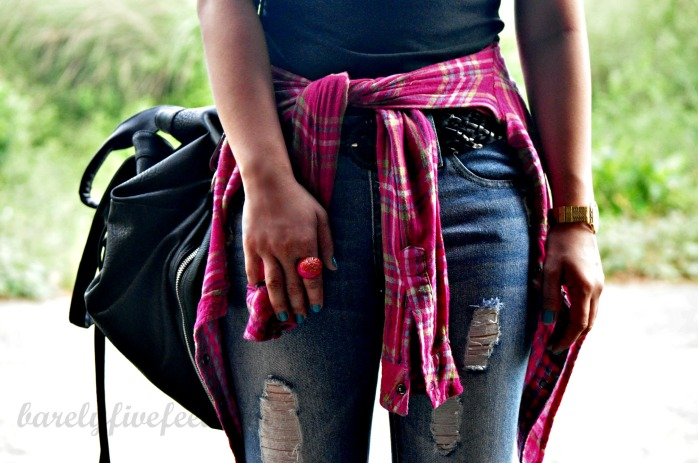 plaid shirt tied around the waist distressed ripped jeans knapsack
